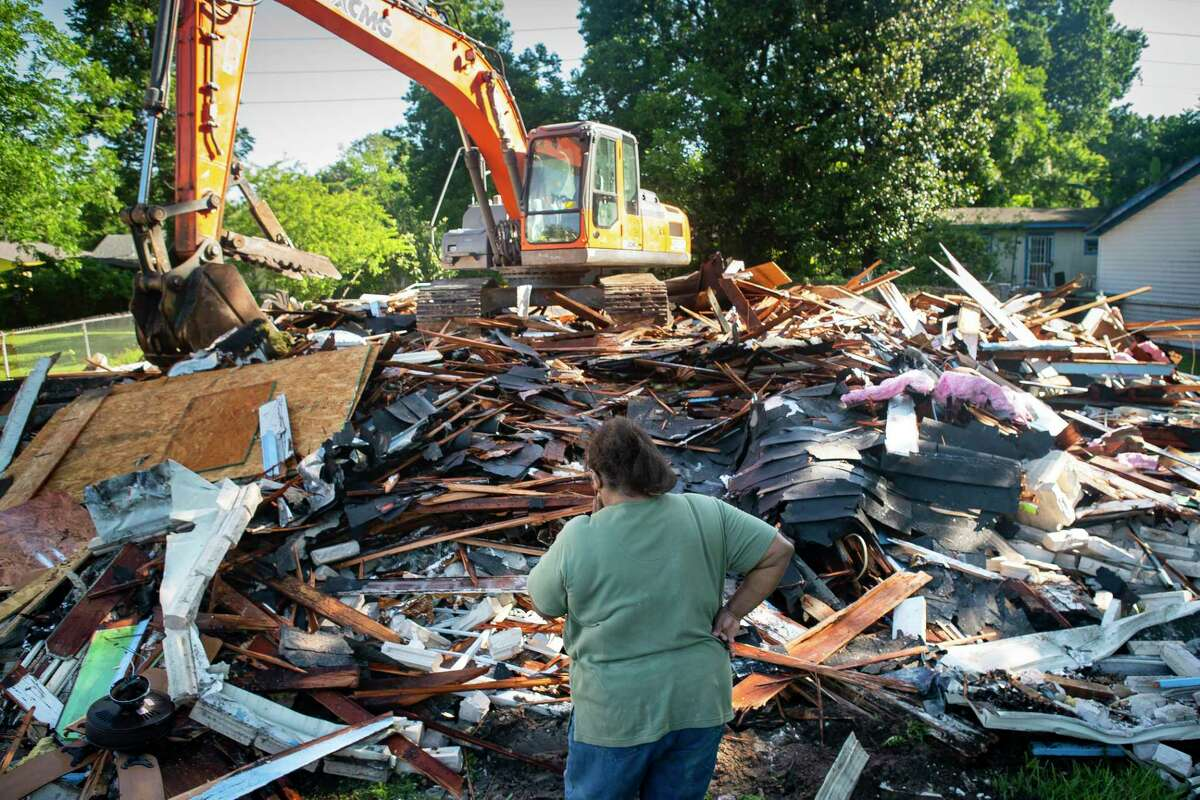 Annie Green looks at the remains of the home where she has lived for 46 years after it was demolished Wednesday morning, May 27, 2020, in Houston. Green's home flooded during Hurricane Harvey, and she has spent the past two years trying to find help rebuilding.