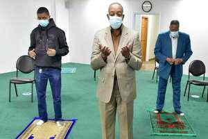 Imam Yahya Abdul-Shakoor, center, with Tariq Sharif, left, and Yusuf Ahmad,right, leads in prayer at the Abdul-Majid Karim Hasan Islamic Center in Hamden Monday.