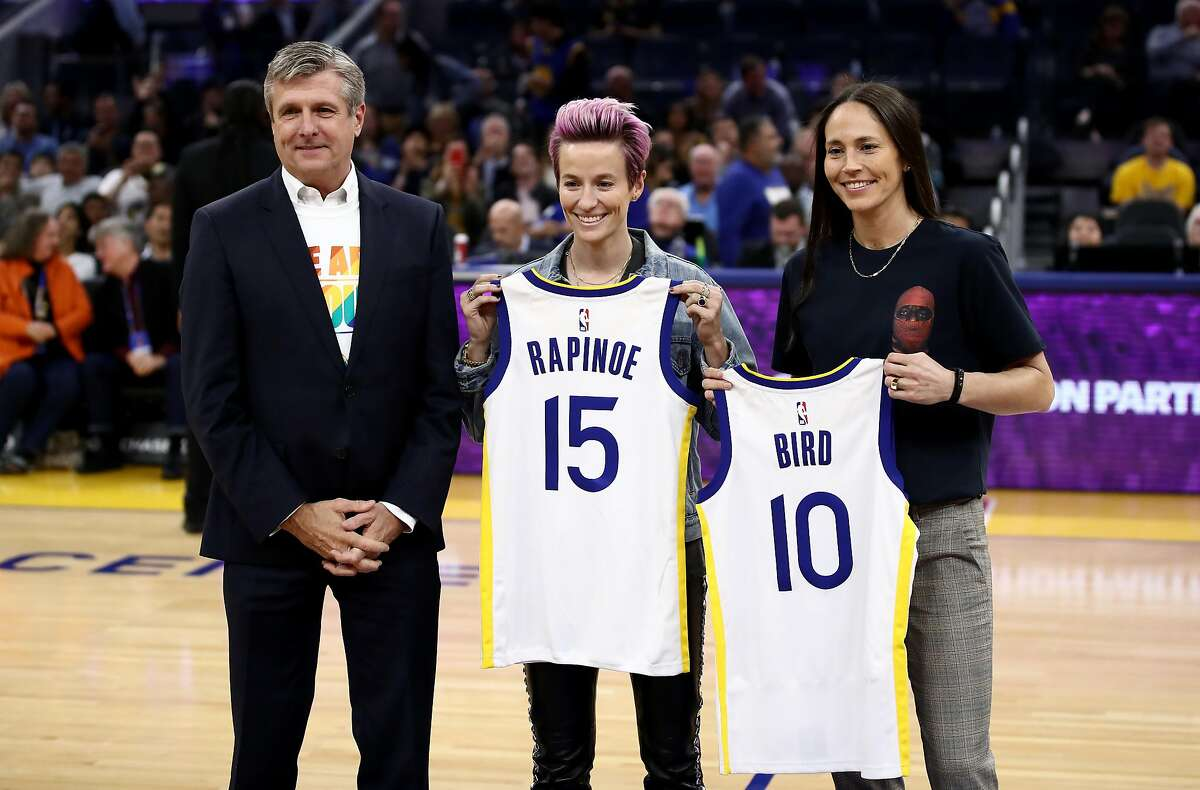SAN FRANCISCO, CALIFORNIA - OCTOBER 30: Soccer star Megan Rapinoe and WNBA star Sue Bird are given Golden State Warriors' jerseys by Warriors President & Chief Operating Officer Rick Welts during a time out of their game against the Phoenix Suns at Chase Center on October 30, 2019 in San Francisco, California. NOTE TO USER: User expressly acknowledges and agrees that, by downloading and or using this photograph, User is consenting to the terms and conditions of the Getty Images License Agreement. (Photo by Ezra Shaw/Getty Images)
