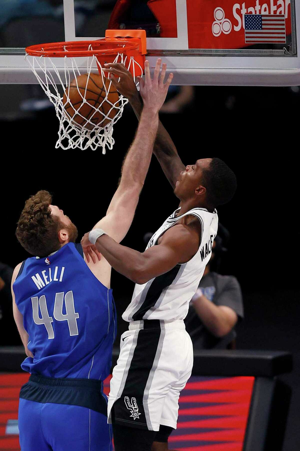 Lonnie Walker of the San Antonio Spurs drives to the basket and draws the foul against Nicolo Melli of the Dallas Mavericks in the second half at American Airlines Center on April 11, 2021 in Dallas.