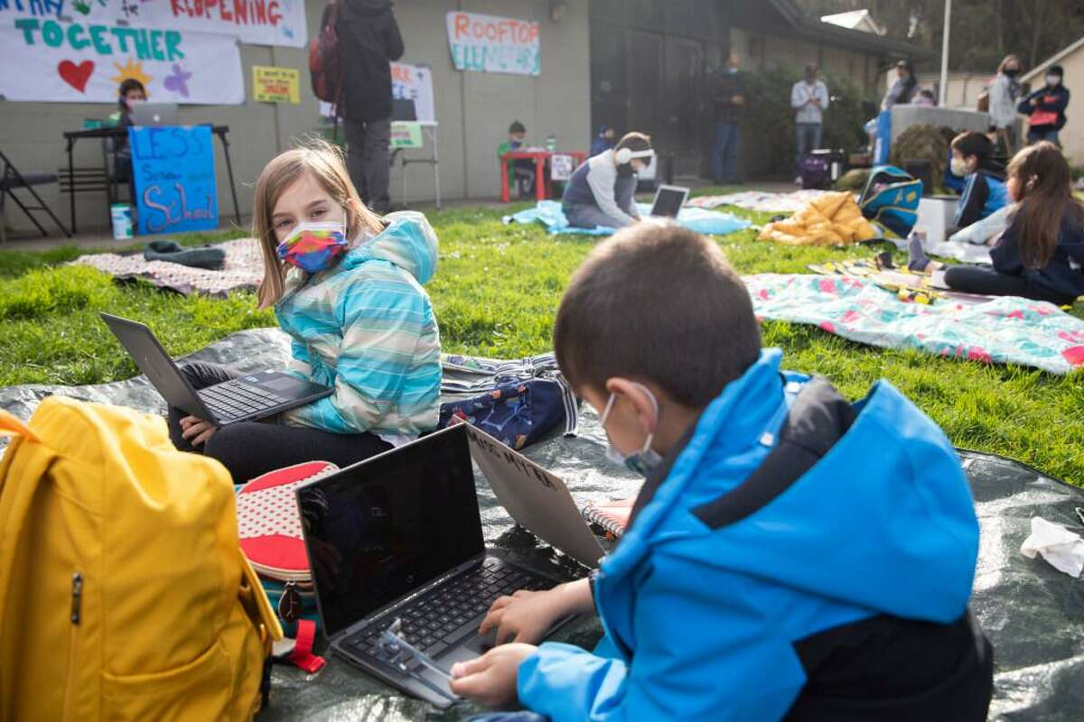 Third-grader Camila Casal (left) and second-grader Santiago Casal attend class on their computers while gathered to advocate for reopening schools at Midtown Terrace Park, across the street from their school, Clarendon Elementary in San Francisco. The SFUSD welcomed its youngest students back into schools on Monday.