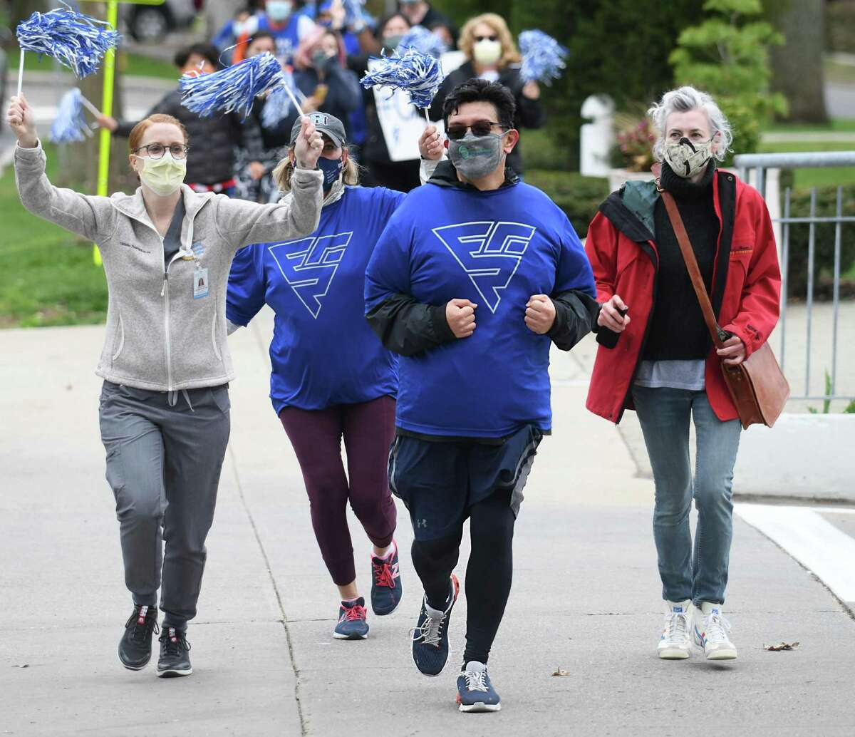 COVID-19 survivor Gabriel Cid, of Greenwich, completes a 5K alongside hospital staff outside Greenwich Hospital in Greenwich, Conn. Monday, April 12, 2021. After spending 37 days at Greenwich Hospital a year ago battling the coronavirus, Cid was discharged on May 18, 2020 becoming the 2,500th COVID patient discharged throughout the Yale New Haven Health system. Cid marked the one year anniversary of the day he was admitted by running a 5K from his home in Byram to Greenwich Hospital where he was joined by doctors, nurses, and other hospital staff to congratulate him on his recovery.