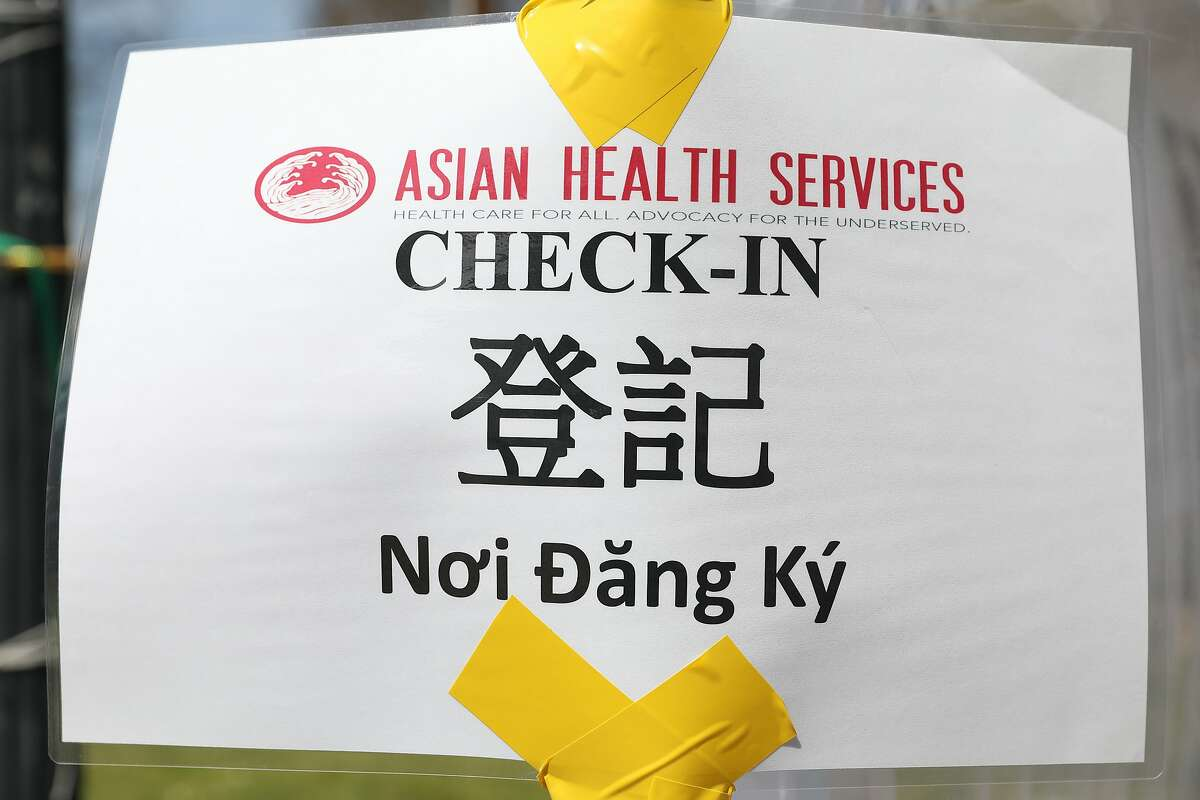 A check-in sign at an Oakland pop-up vaccination clinic, sponsored by Asian Health Services is in English, Chinese and Vietnamese.