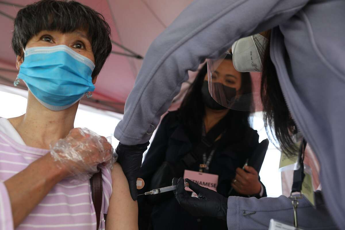 Cecilia Lam (left) receives a COVID-19 vaccine as Thu Quach, chief deputy of administration, helps interpret for her at a pop-up vaccination clinic sponsored by Asian Health Services on April 12 in Oakland.