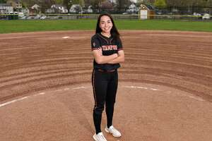 Pitcher Kim Saunders, a senior, poses on the softball field at Stamford High School in Stamford, Conn. Monday, April 12, 2021. Saunders recently committed to play college softball at Bentley University, a Division II school in Waltham, Mass.