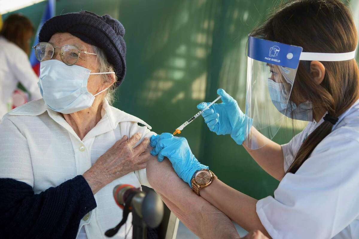 Nhuong Le, 81, receives the Johnson & Johnson COVID-19 vaccine from Kroger pharmacist Stephanie Phan at Thái Xuân Village condominiums near Hobby Airport Sunday, April 11, 2021 in Houston. Asians are slightly over-represented among vaccine recipients in Harris County, but ZIP code 77061 has one of the lowest vaccination rates.