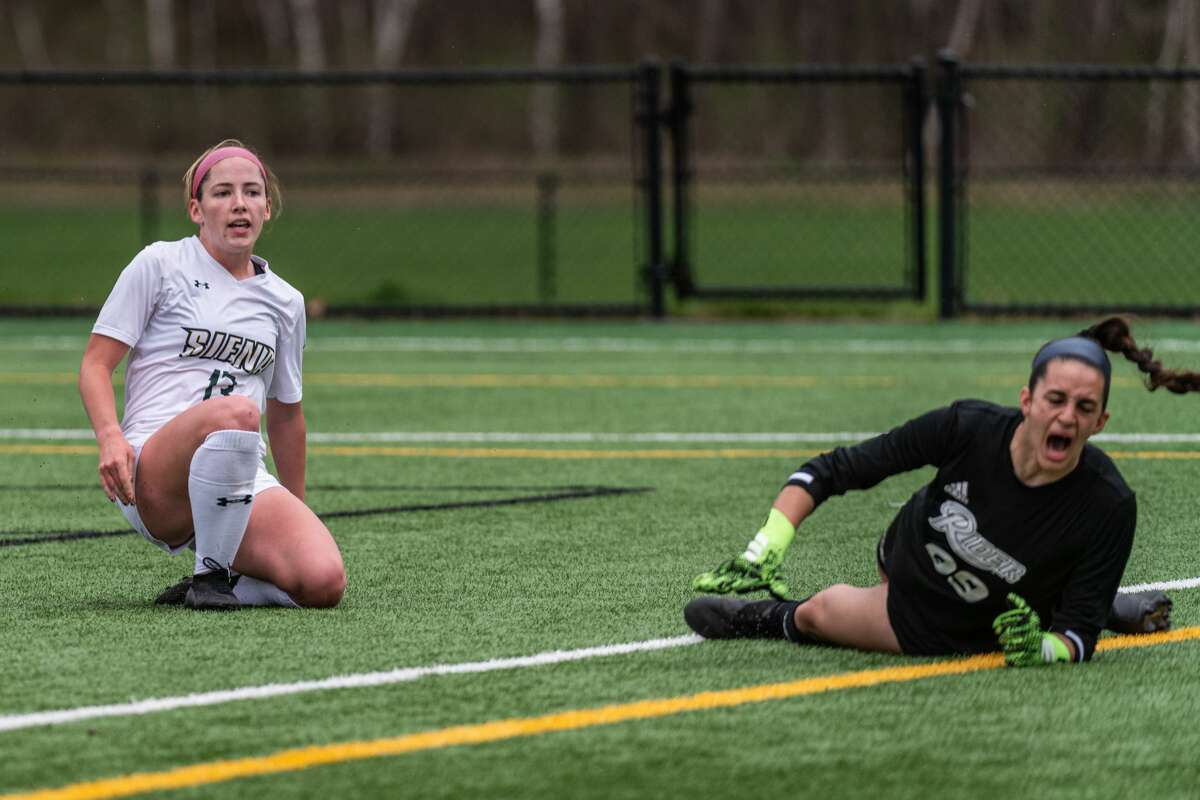 Carrie Krohn of Siena watches her shot go in the goal past Rider goalie Ellie Sciancalepore on Monday, April 12, 2021. (Robert Simmons / Siena Athletics)