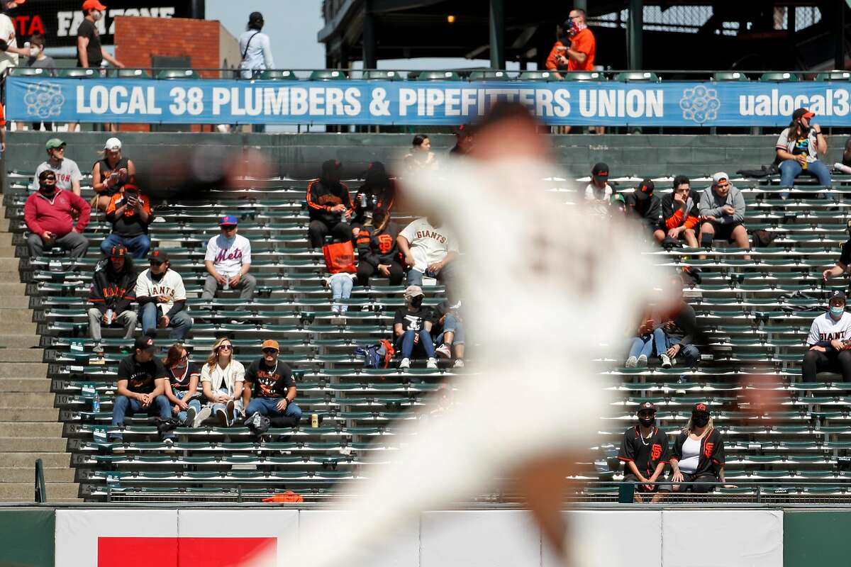 As socially distanced fans watch in left field bleachers, San Francisco Giants' Anthony DeSclafini winds up to pitch against the Colorado Rockies on April 11.