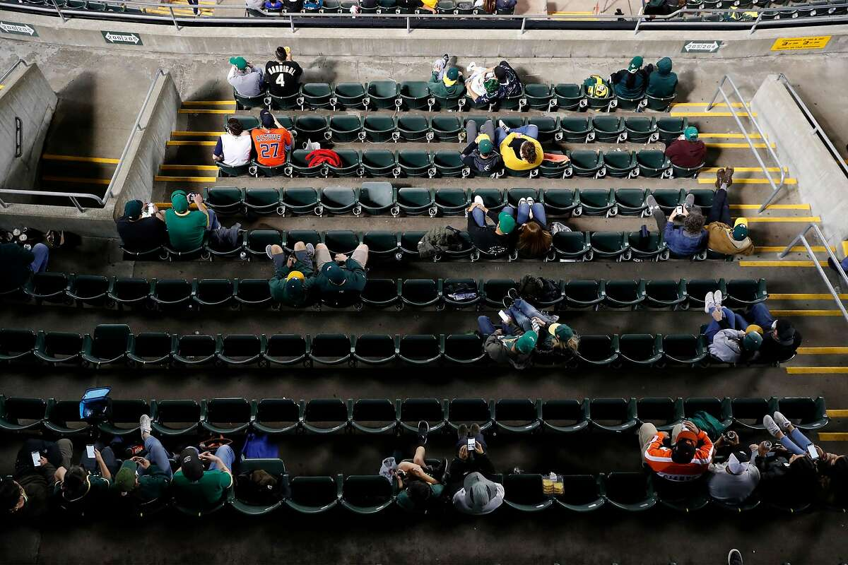 Fans sit in social distanced groups as Oakland Athletics play Houston Astros in season opener at Oakland Coliseum in Oakland, Calif., on Thursday, April 1, 2021.
