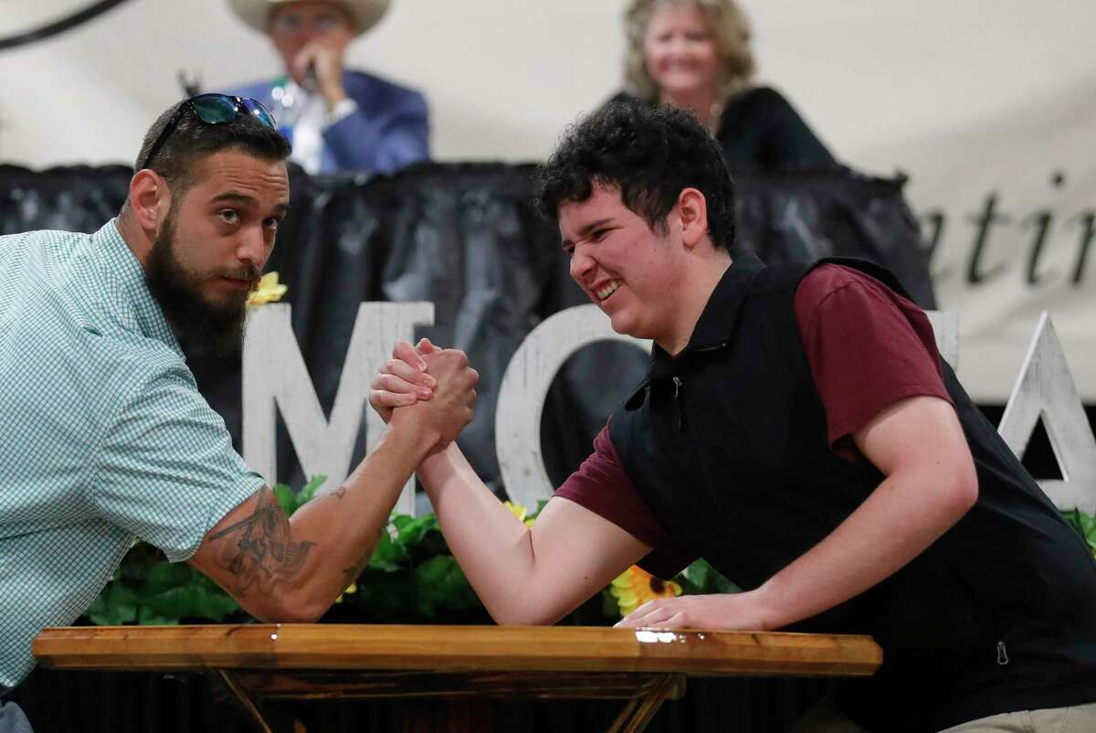 Ambrose Leims of Willis High School has an arm wrestle on the table he won grand champion handicraft I on as it's auctioned off during the non-livestock auction at the Montgomery County Fair and Rodeo, Monday, April 12, 2021, in Conroe.