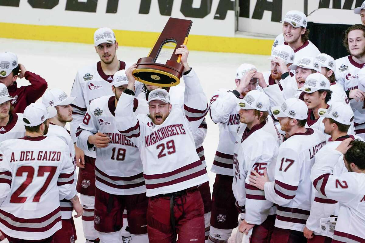 UMass' George Mika (29) holds the NCAA trophy over his head as he skates with the team to celebrate their 5-0 win over St. Cloud State in the Frozen Four championship game Saturday.
