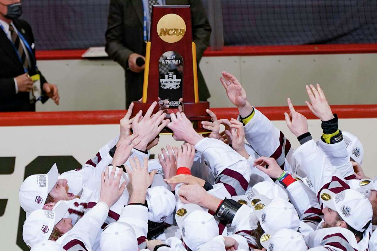 The UMass hockey team reaches for the NCAA trophy while captain Jake Gaudet holds it over his head as the team celebrates defeating St. Cloud State to win the Frozen Four championship game Saturday.