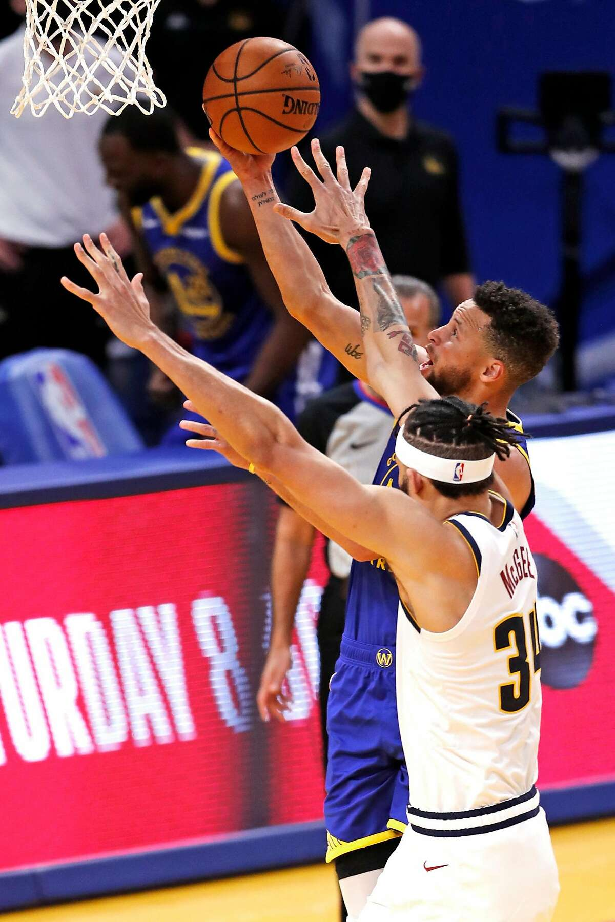 Golden State Warriors' Stephen Curry scores a basket against Denver Nuggets' JaVale McGee, passing Wilt Chamberlain for most points in franchise history, during 1st quarter of NBA game at Chase Center in San Francisco, Calif., on Monday, April 12, 2021.