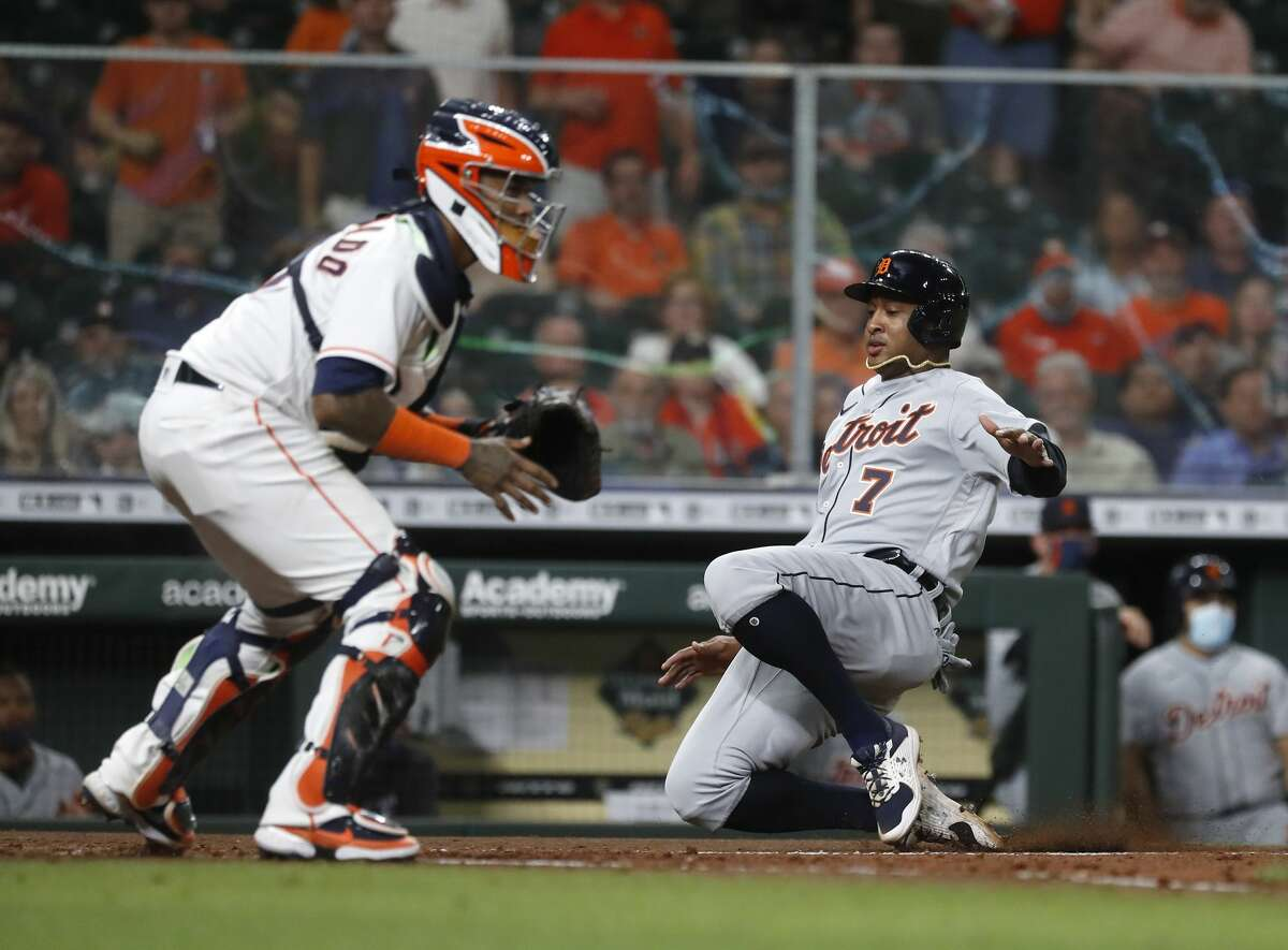 Detroit Tigers Jonathan Schoop (7) slides home to score a run on Grayson Greiner's single against Houston Astros catcher Martin Maldonado (15) during the fifth inning of an MLB baseball game at Minute Maid Park, in Houston, Monday, April 12, 2021.