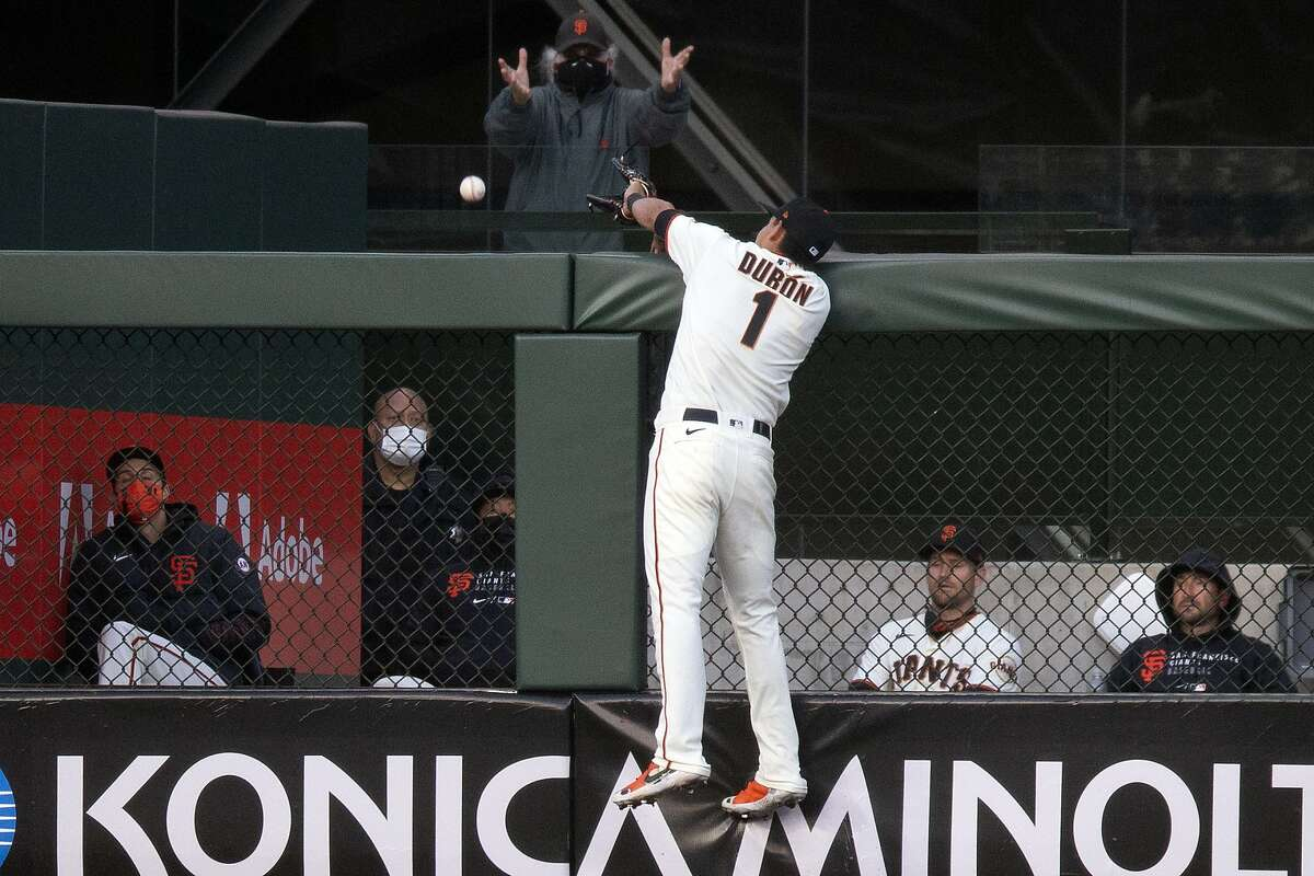 San Francisco Giants infielder Mauricio Dubón (1) leaps in vain for a two-run home run hit by Cincinnati Reds' Jesse Winker during the third inning of a baseball game, Monday, April 12, 2021, in San Francisco, Calif.