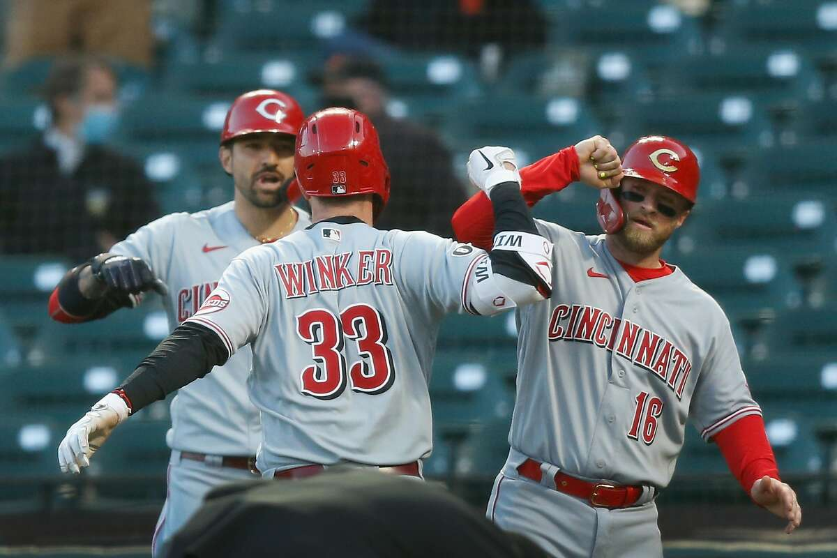 Jesse Winker #33 of the Cincinnati Reds celebrates with Tucker Barnhart #16 after hitting a two-run home run in the top of the third inning against the San Francisco Giants at Oracle Park on April 12, 2021 in San Francisco, California.