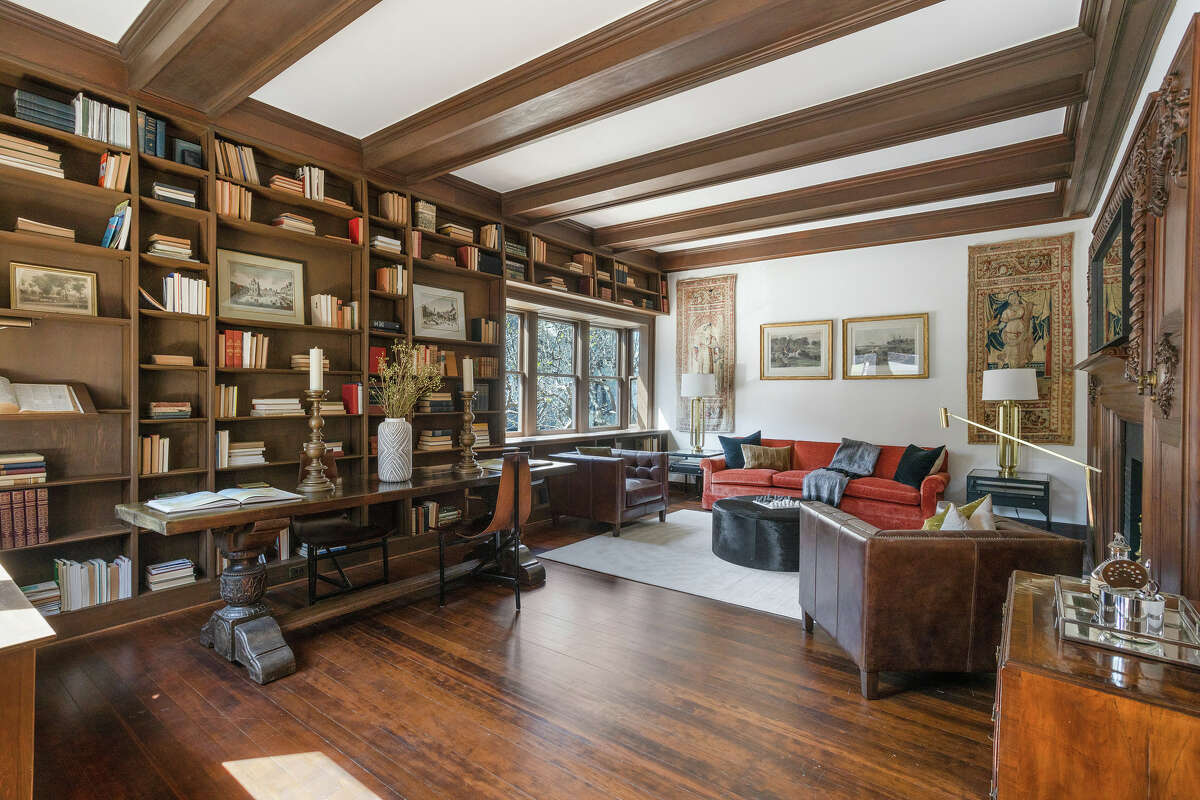 A sitting room and library offer built-in bookshelves from floor to beamed ceiling.