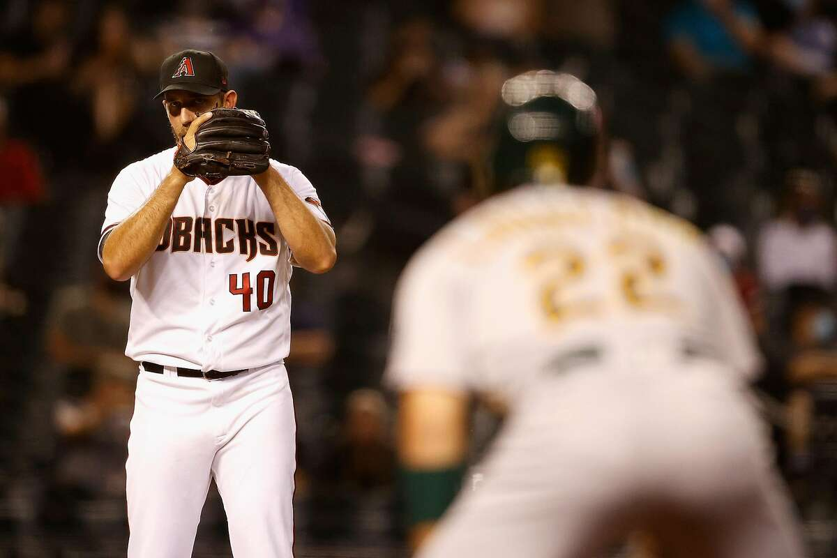PHOENIX, ARIZONA - APRIL 12: Starting pitcher Madison Bumgarner #40 of the Arizona Diamondbacks looks at Ramon Laureano #22 of the Oakland Athletics as he leads off first base during the fifth inning of the MLB game at Chase Field on April 12, 2021 in Phoenix, Arizona. (Photo by Christian Petersen/Getty Images)