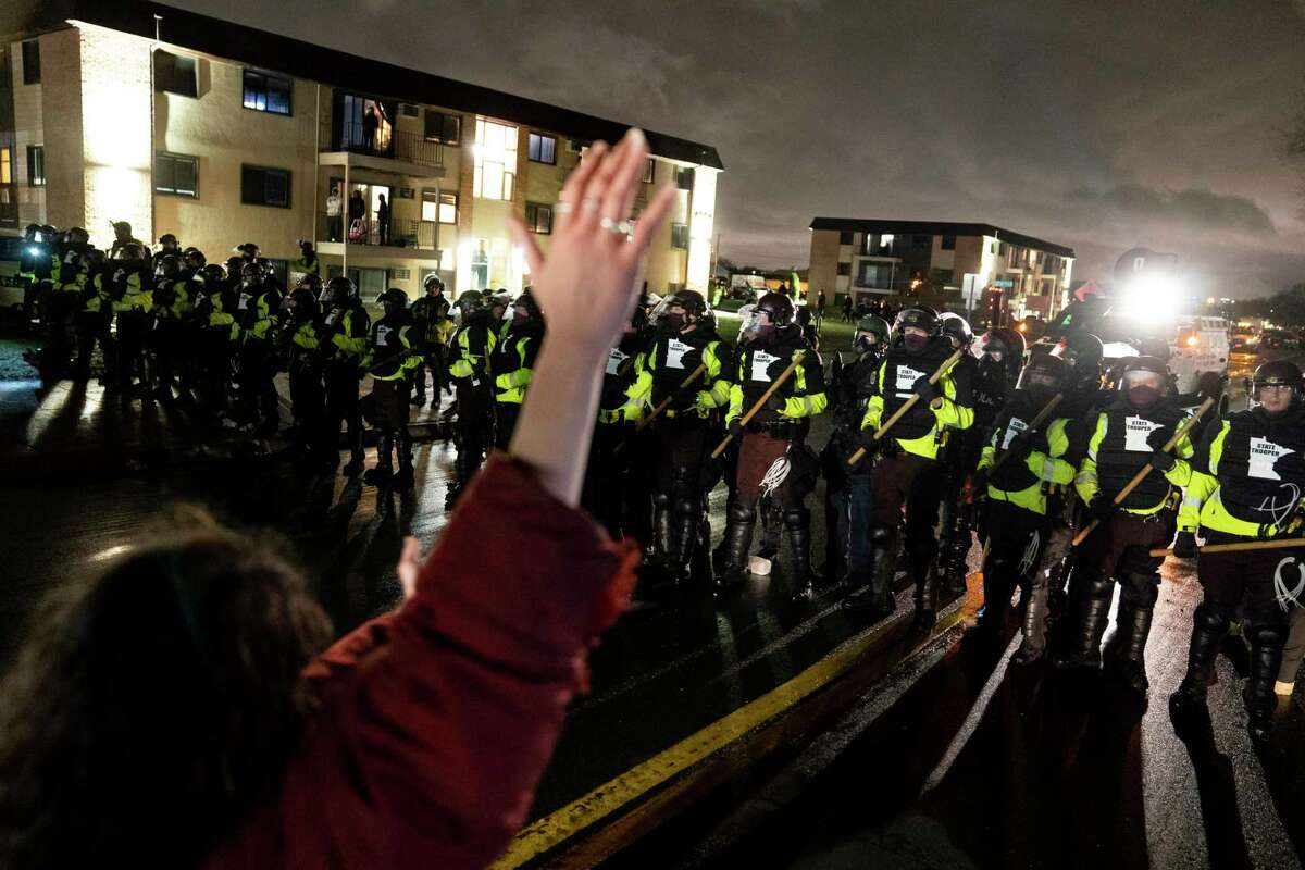 A demonstrator raises their hand while facing off against a perimeter of police as they defy an order to disperse during a protest against the police shooting of Daunte Wright, late Monday, April 12, 2021, in Brooklyn Center, Minn.