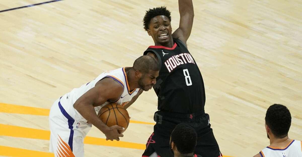 Phoenix Suns guard Chris Paul grabs the lose ball as Houston Rockets forward Jae'Sean Tate (8) defends during the first half of an NBA basketball game, Monday, April 12, 2021, in Phoenix. (AP Photo/Matt York)