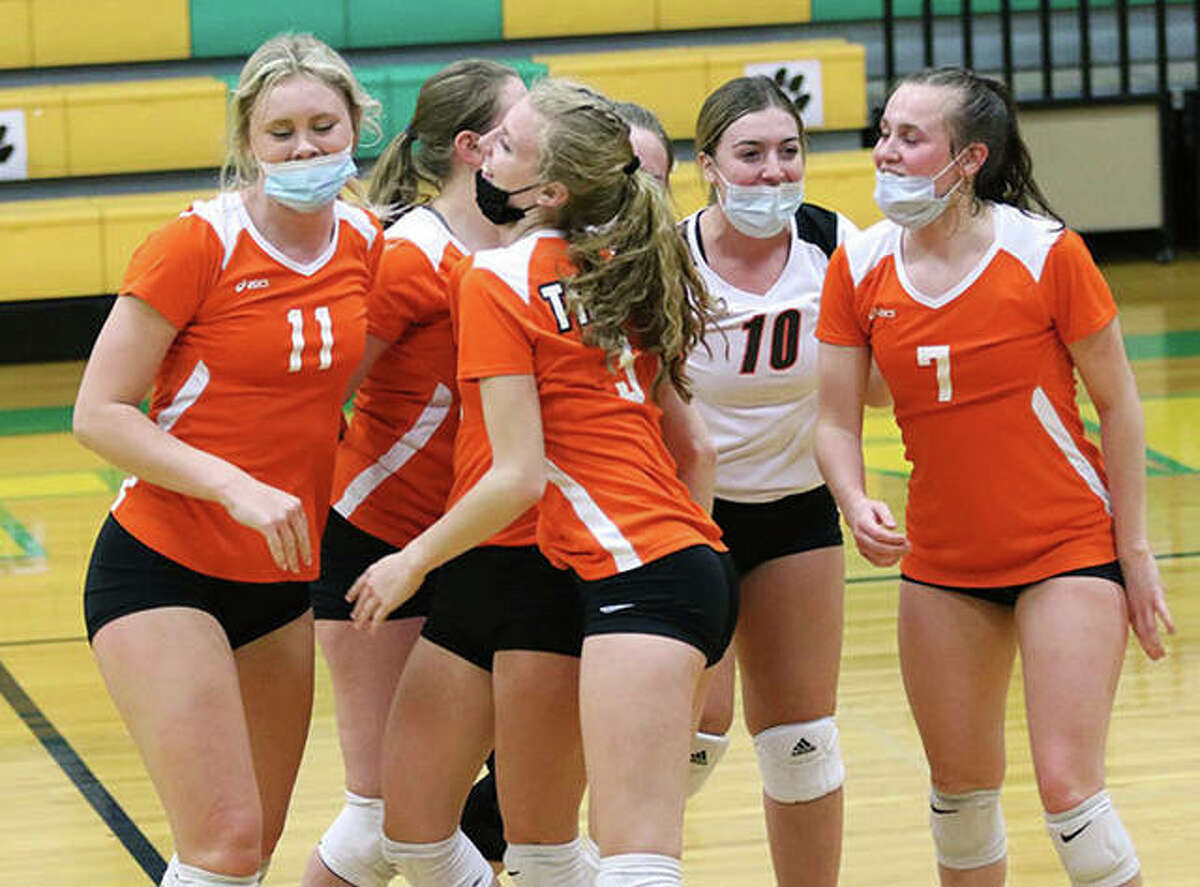 Greenfield's Kersty Gibbs (11), Alexis Pohlman (3), Hannah Theivagt (10) and Baylee Bilbruck (7) celebrate with teammates on the court after set point in game one of their two-set victory over Raymond Lincolnwood on Monday night in Palmyra.