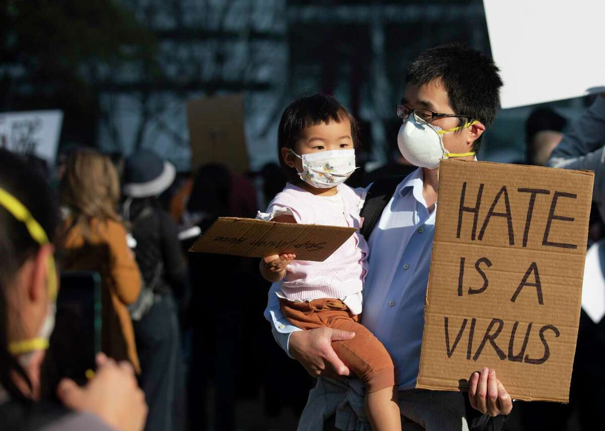 Meiling Liu takes a photograph of her husband and daughter, Zhimin Huang and Charlotte Liu, at the March