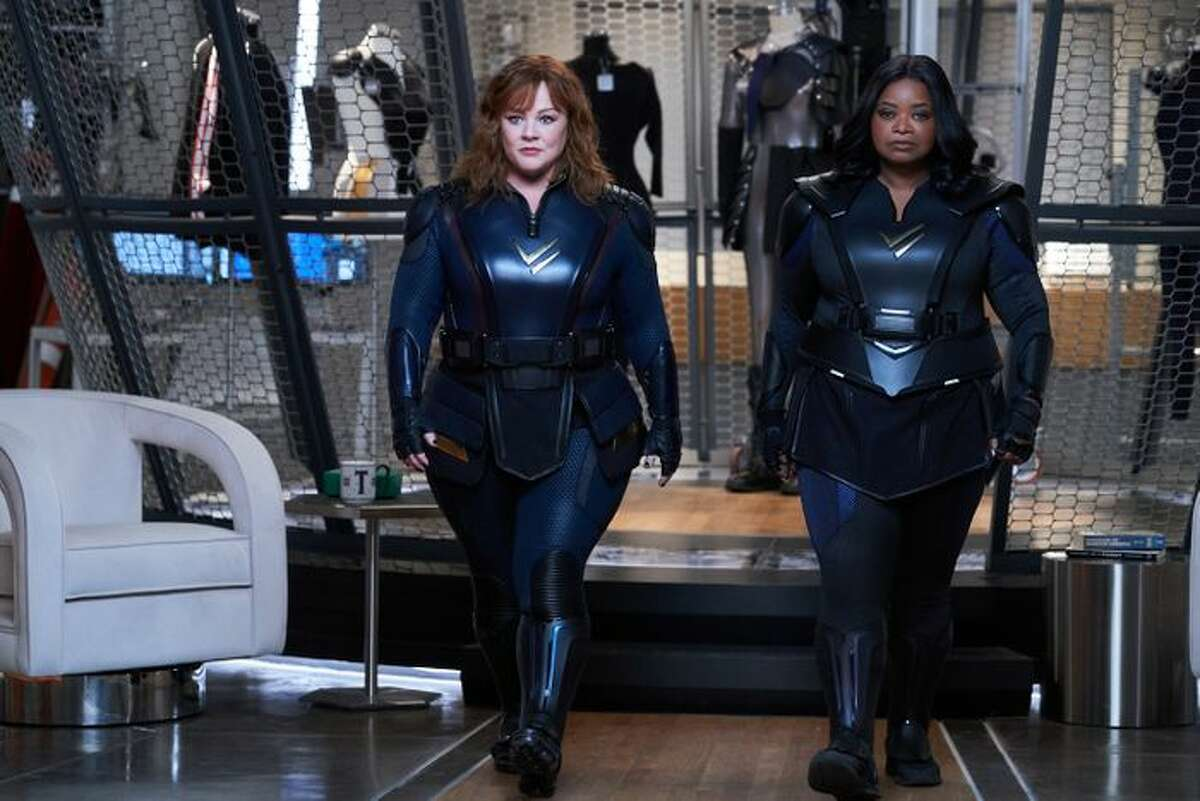 """A displeased-looking Melissa McCarthy and Octavia Spencer, perhaps approaching their """"Thunder Force"""" writer-director Ben Falcone (McCarthy's husband) to discuss what they think of the costumes he chose for them?"""