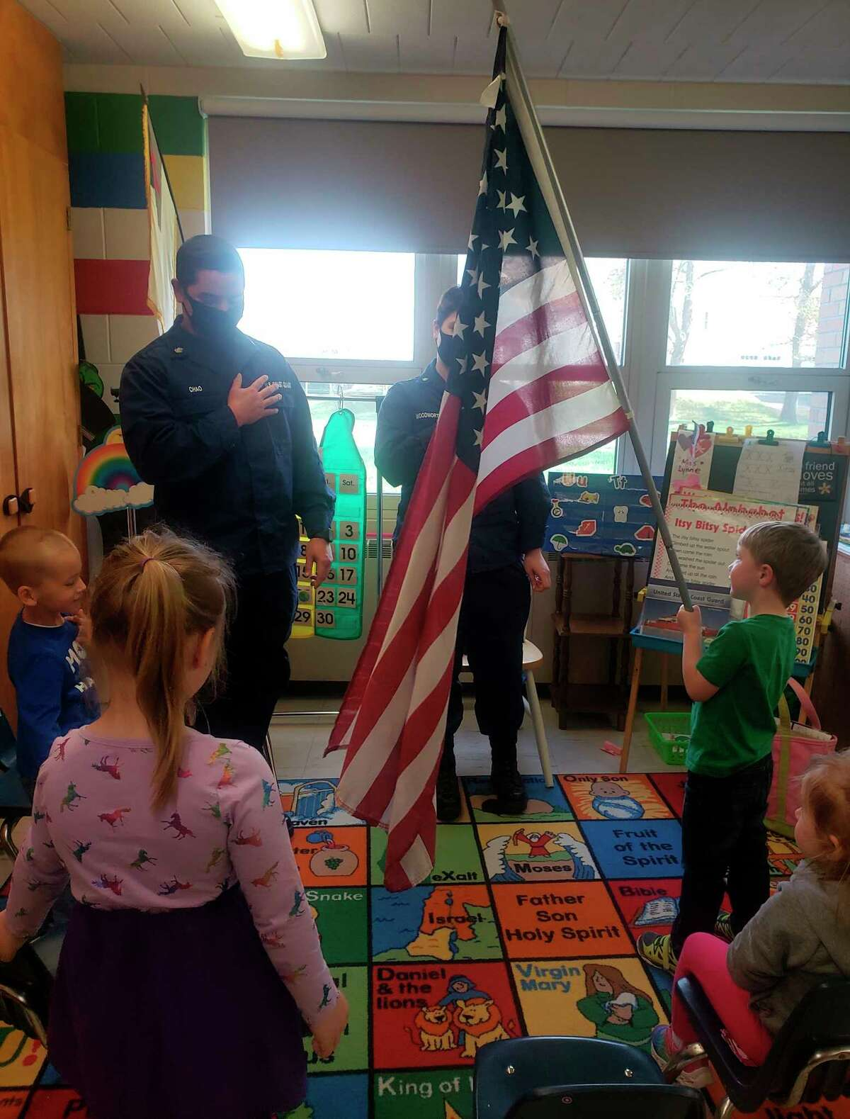 Lynne Gatz's preschool students say the Pledge of Allegiance with two members of the U.S. Coast Guard at Trinity Lutheran School on Monday. (Courtesy photo)