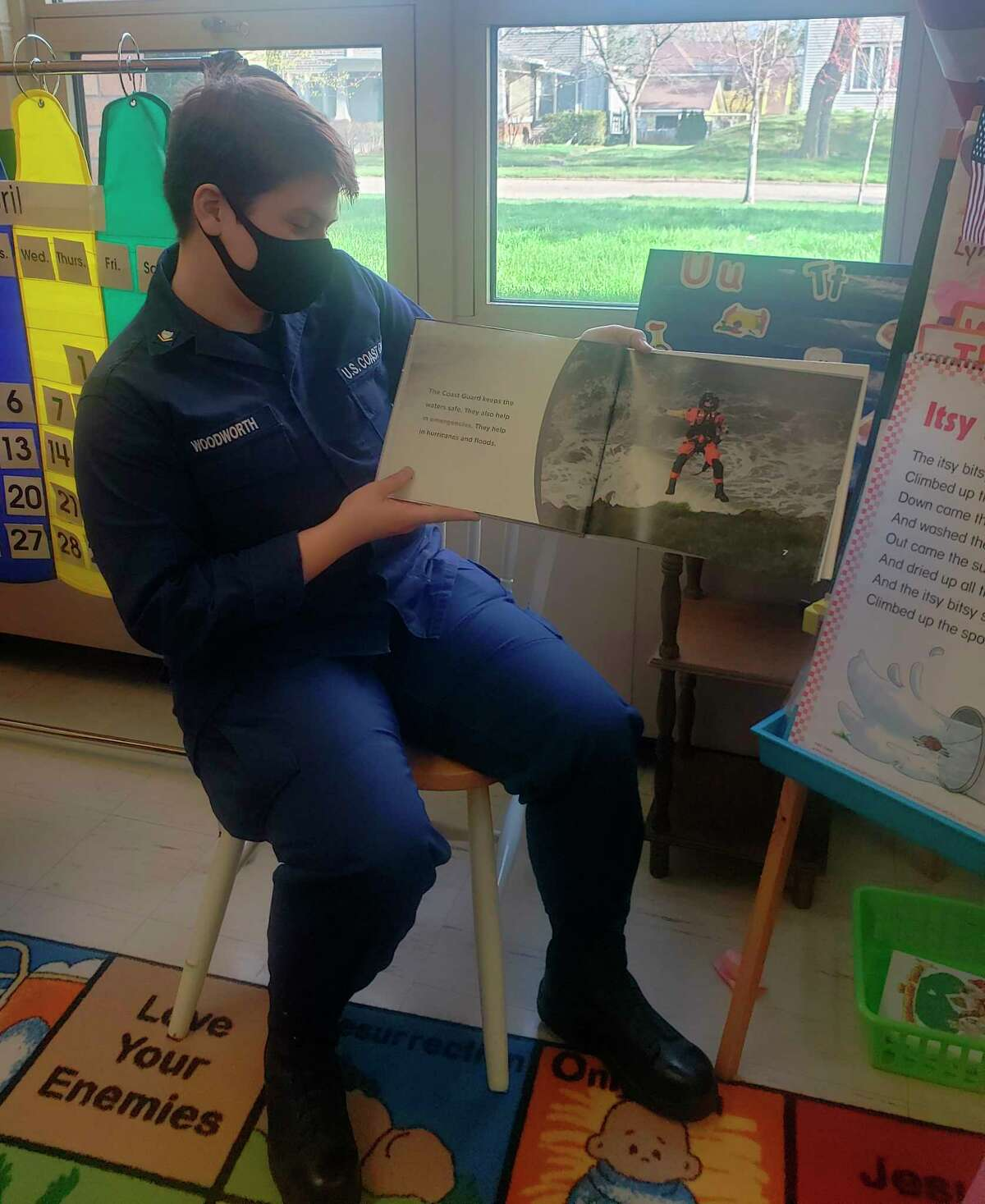 A member of the U.S. Coast Guard reads a book to preschool students at Trinity Lutheran School on Monday. (Courtesy photo)