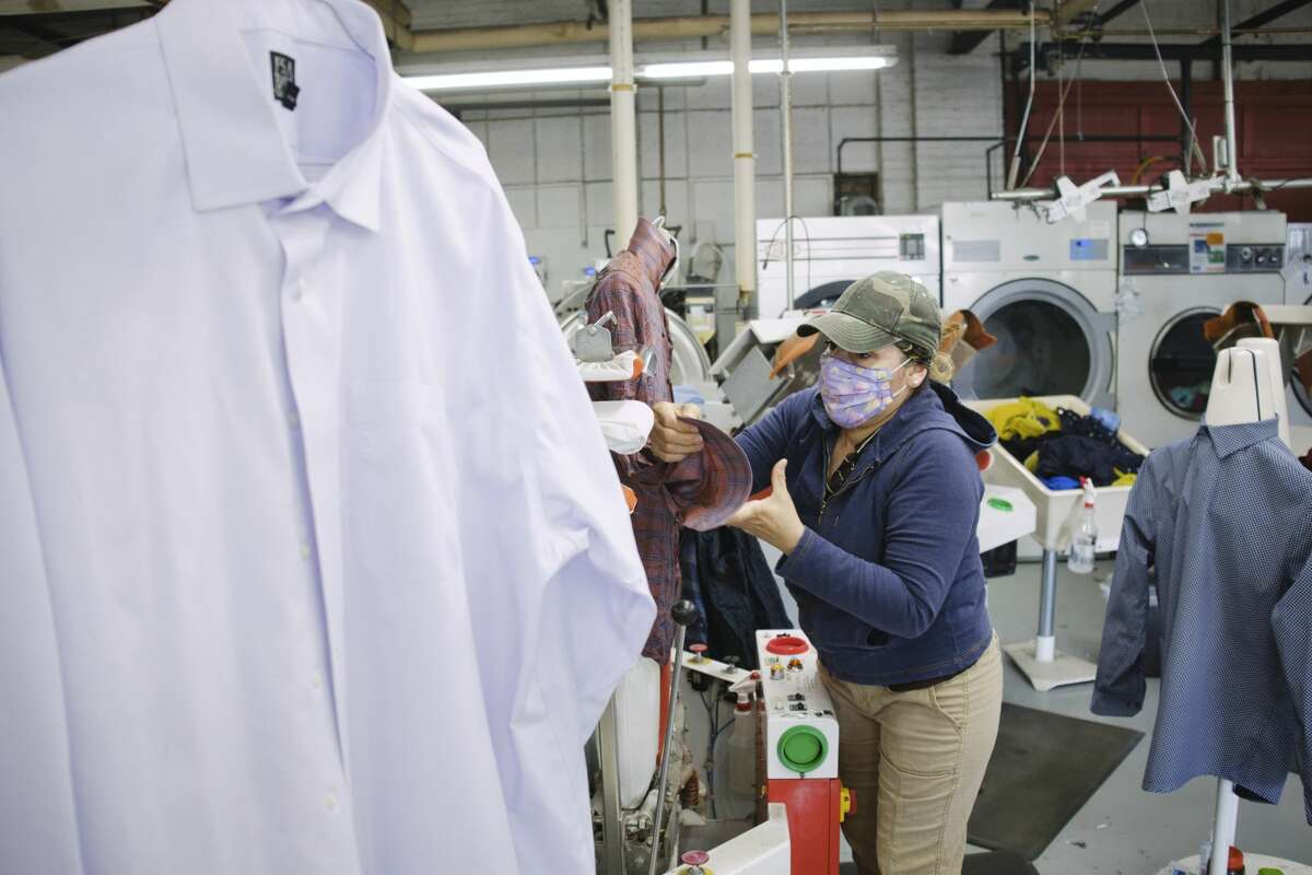 Best Cleaners presser Sandra Thomas operates a double buck automated shirt press at the State St. production facility on Tuesday, April 13, 2021, in Schenectady, N.Y. (Paul Buckowski/Times Union)