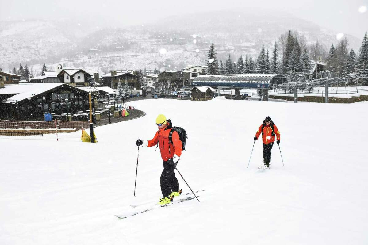 Skiers ski up an empty run at a Vail Resorts Inc. location in Vail, Colo., on March 19, 2020.