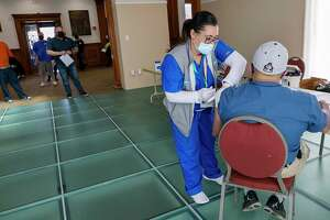 Griffin Hospital nurse Carrie Cotto administers the Johnson & Johnson COVID-19 vaccine to Reinaldo Vazquez, of Meriden, Conn., during a clinic at the Augusta Curtis Cultural Center on Wednesday, April 7, 2021. (Dave Zajac /Record-Journal via AP)