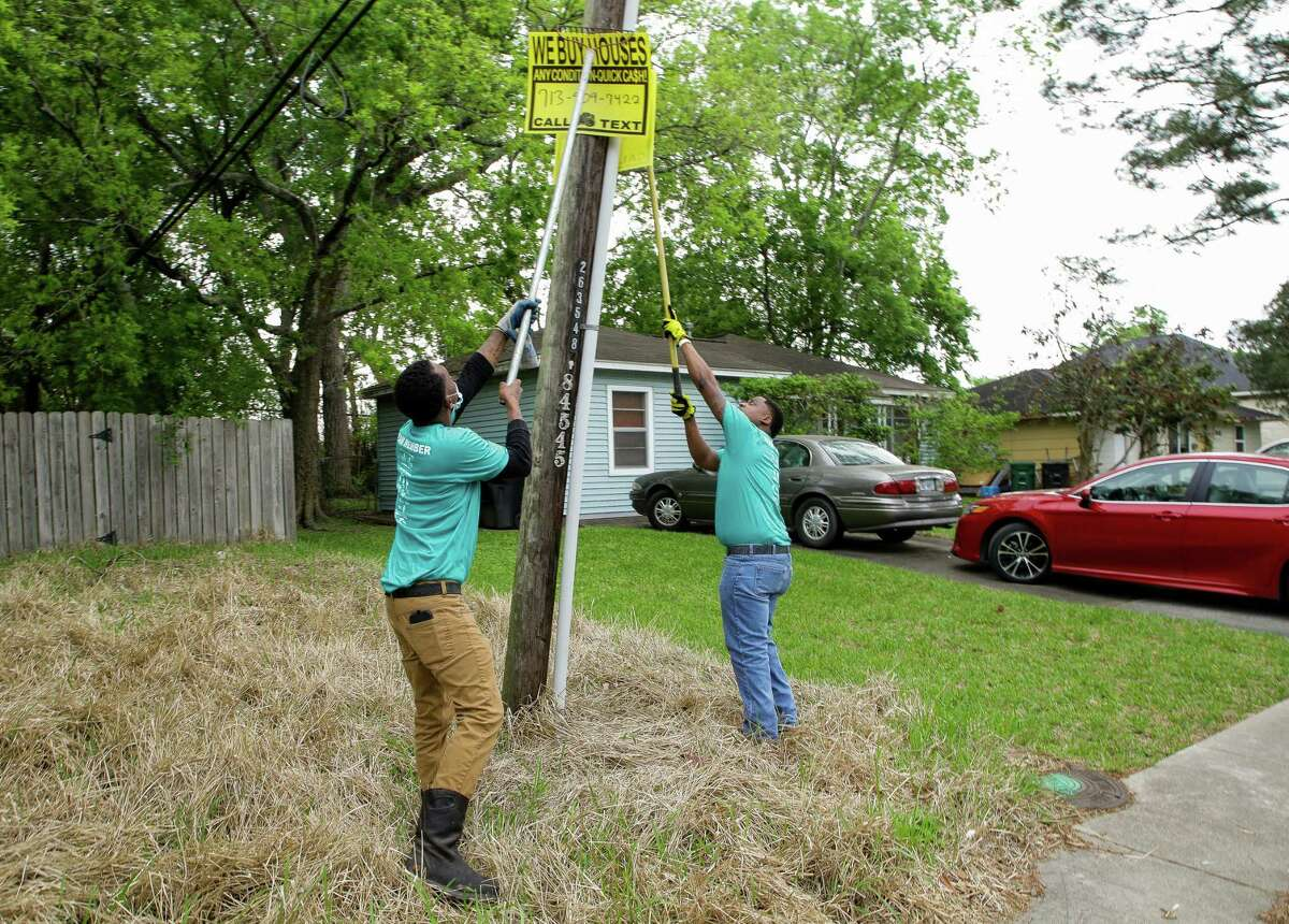 Eddie Dancy, left, and Royce Hogan - both with the District K team devoted to community cleanup - take down a bandit sign on April 10, 2021, in Houston. A bill in Austin would significantly increase the penalties on hanging the signs from $1,000 maximum to up to $5,000 for a second offense and $10,000 for a third and thereafter.