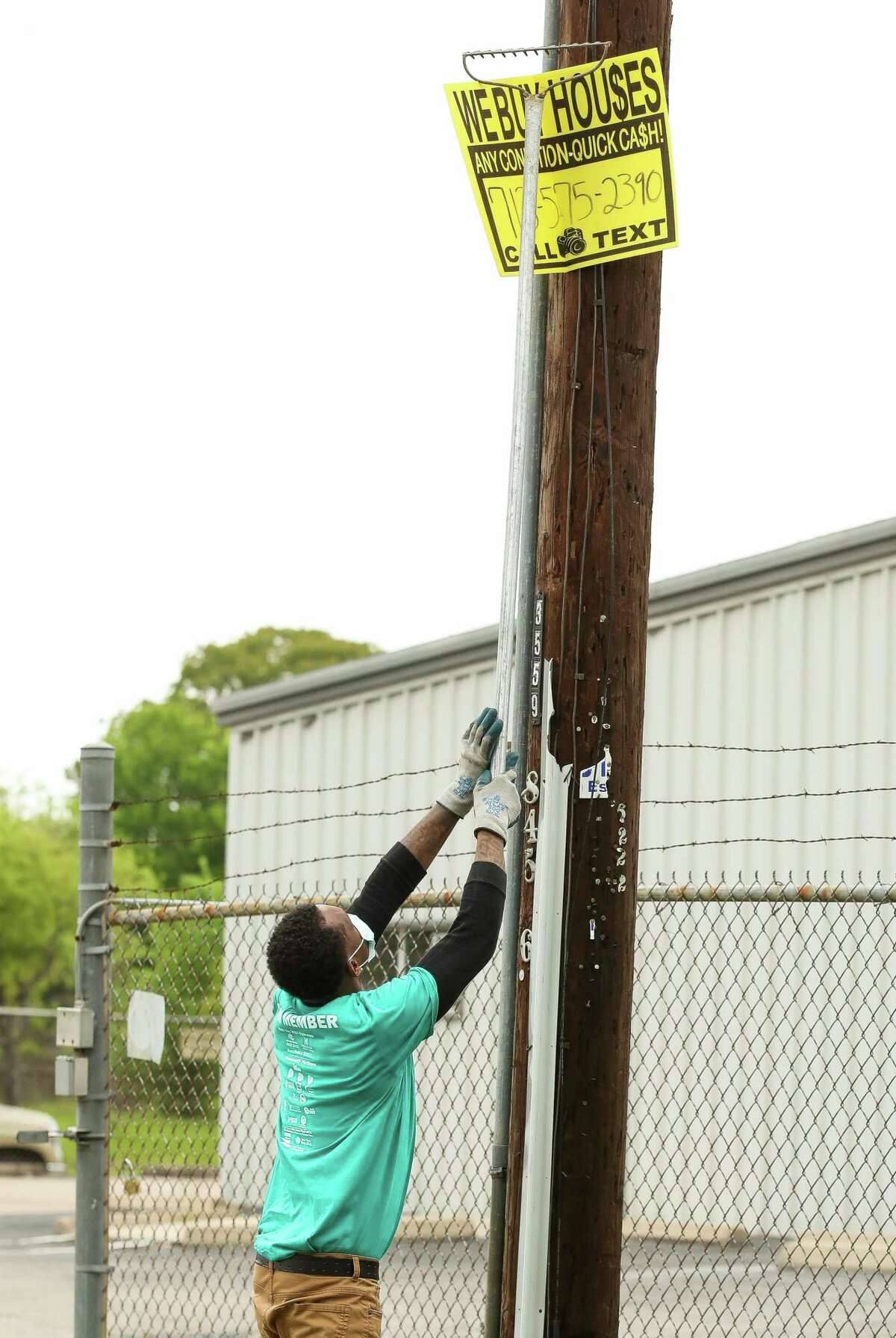 Eddie Dancy - with the District K community cleanup team - takes down a bandit sign from an electrical post on April 10, 2021, in Houston. A bill in Austin would significantly increase the penalties on hanging the signs from $1,000 maximum to up to $5,000 for a second offense and $10,000 for a third and thereafter.