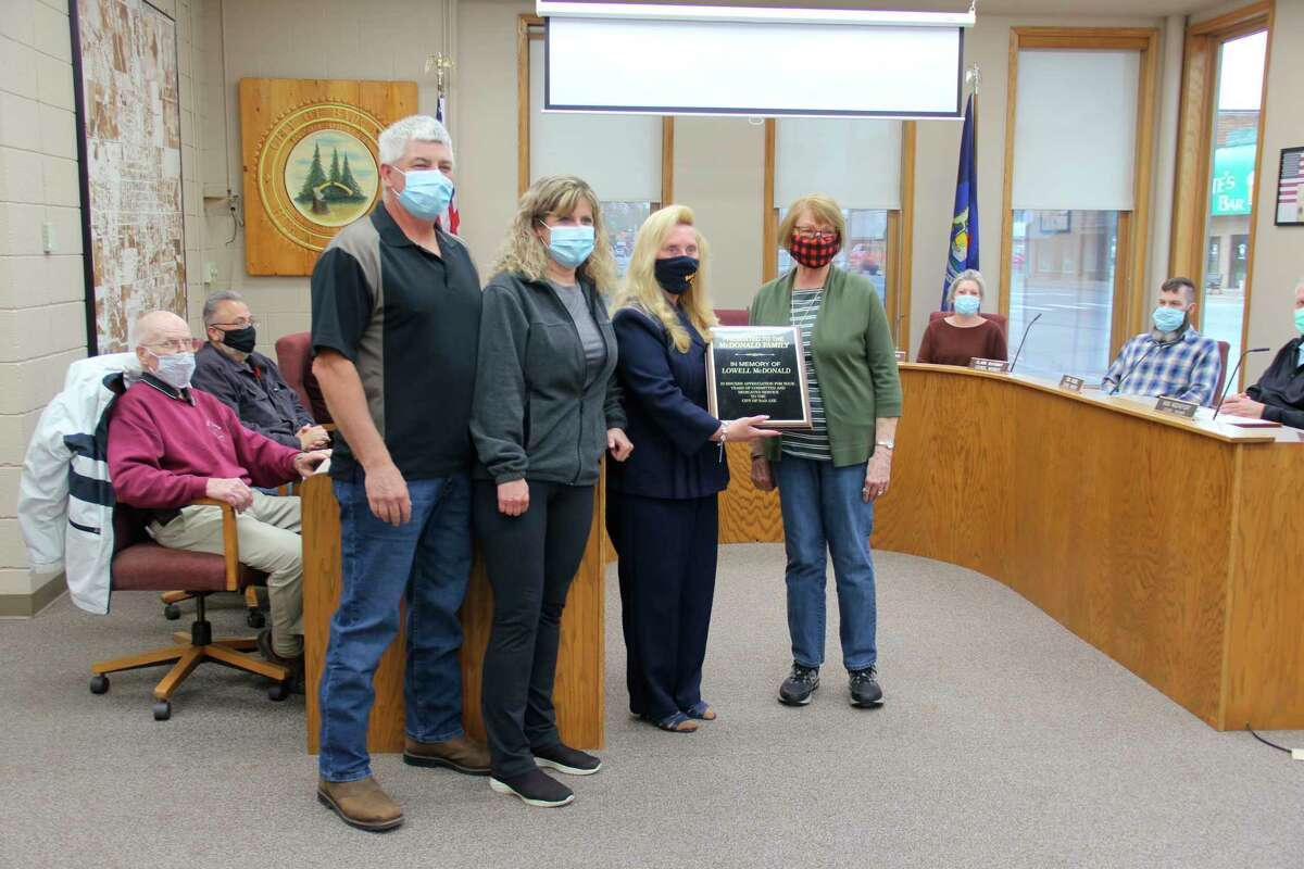 Bad Axe Mayor Kathleen Particka presents an award to the family of Lowell McDonald, who died earlier this year. McDonald was best known in the area as the owner of the McDonald's Food and Family grocery store. (Robert Creenan/Huron Daily Tribune)