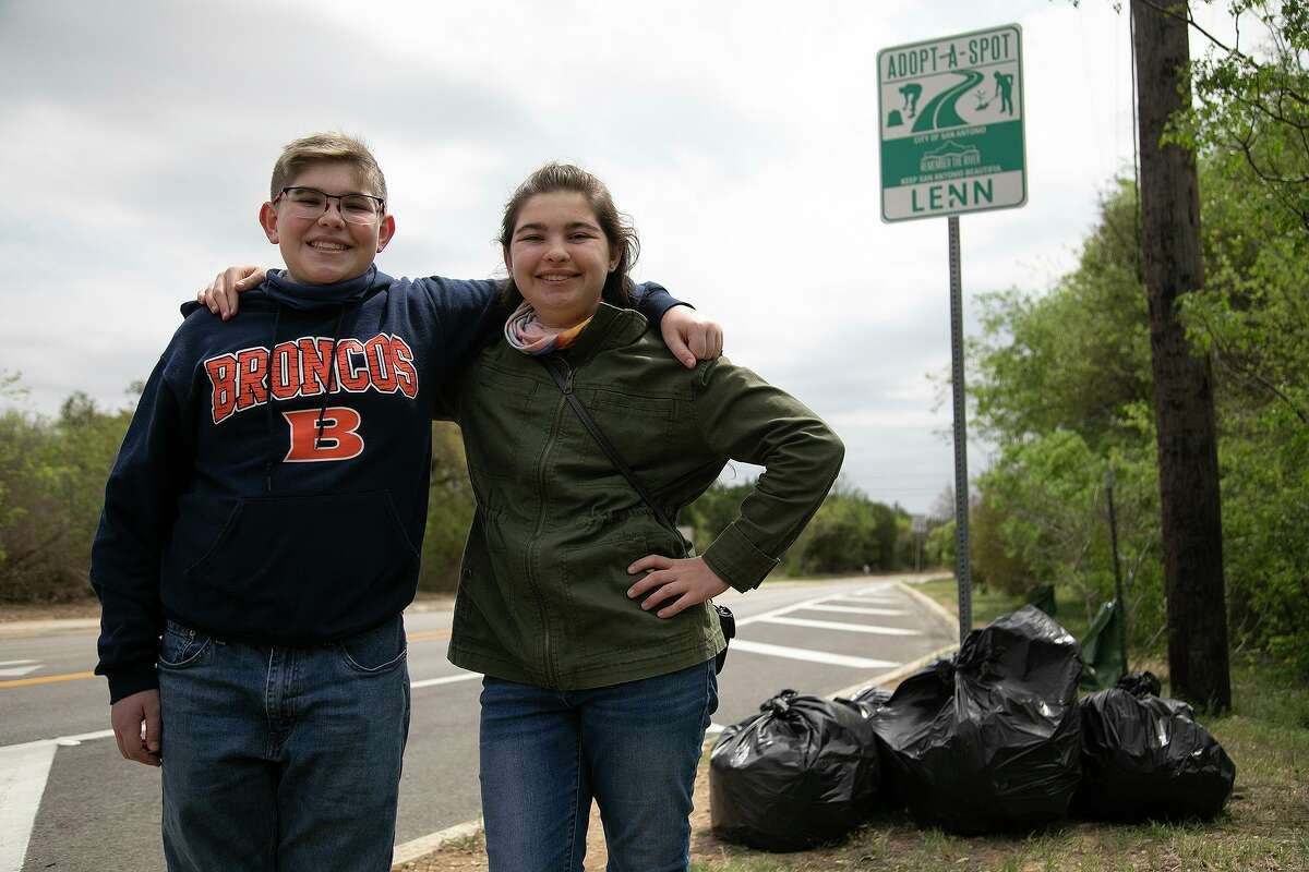 Nichole Dopp, 17, and her brother, Louis Dopp, 14, stand next to bags of trash they picked up along the section of Kyle Seale Parkway their family has adopted to keep clean.