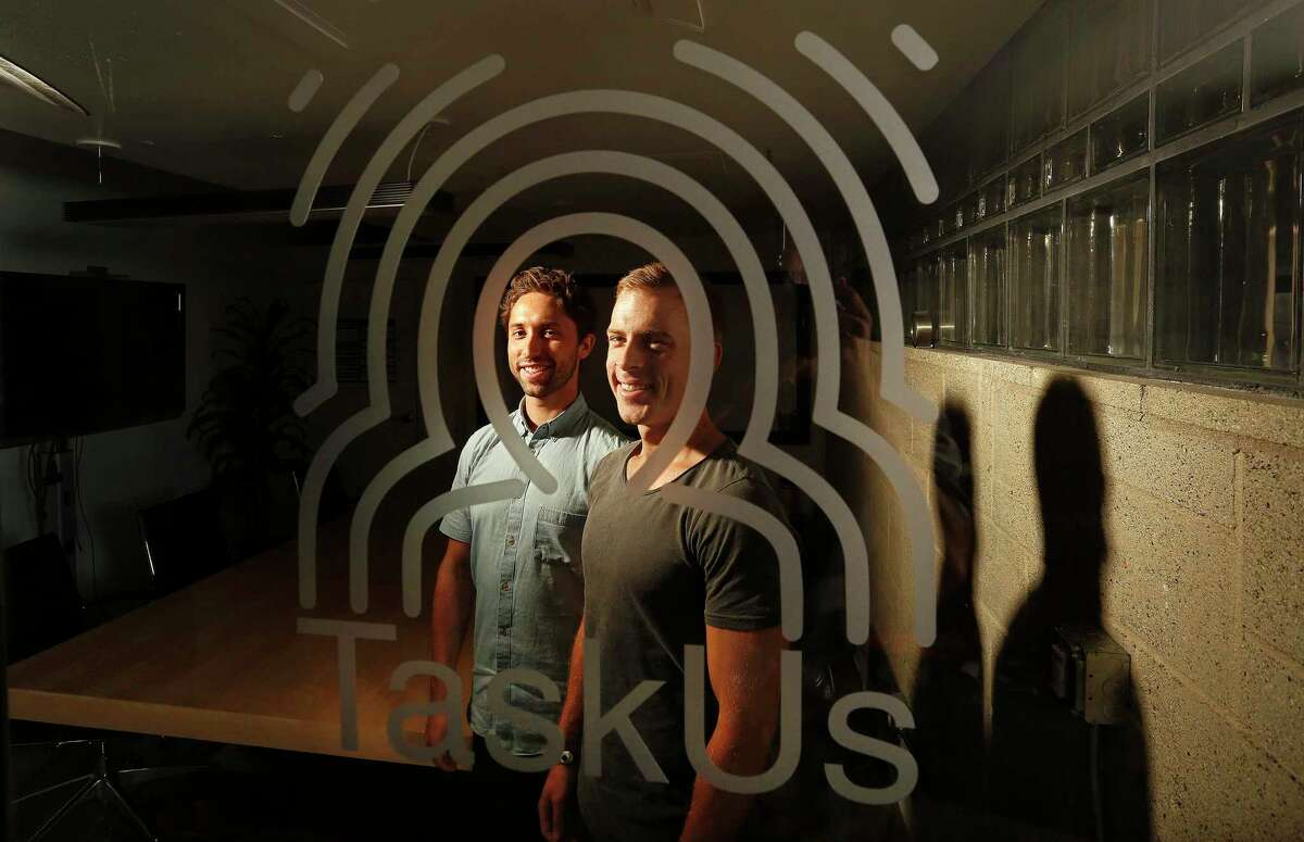 In this Aug. 5, 2015 photo, Jaspar Weir, 29, left, and Bryce Maddock, 29, the co-founders of TaskUs, pose for a portrait inside the conference room at thier former headquarters in Santa Monica, Calif.