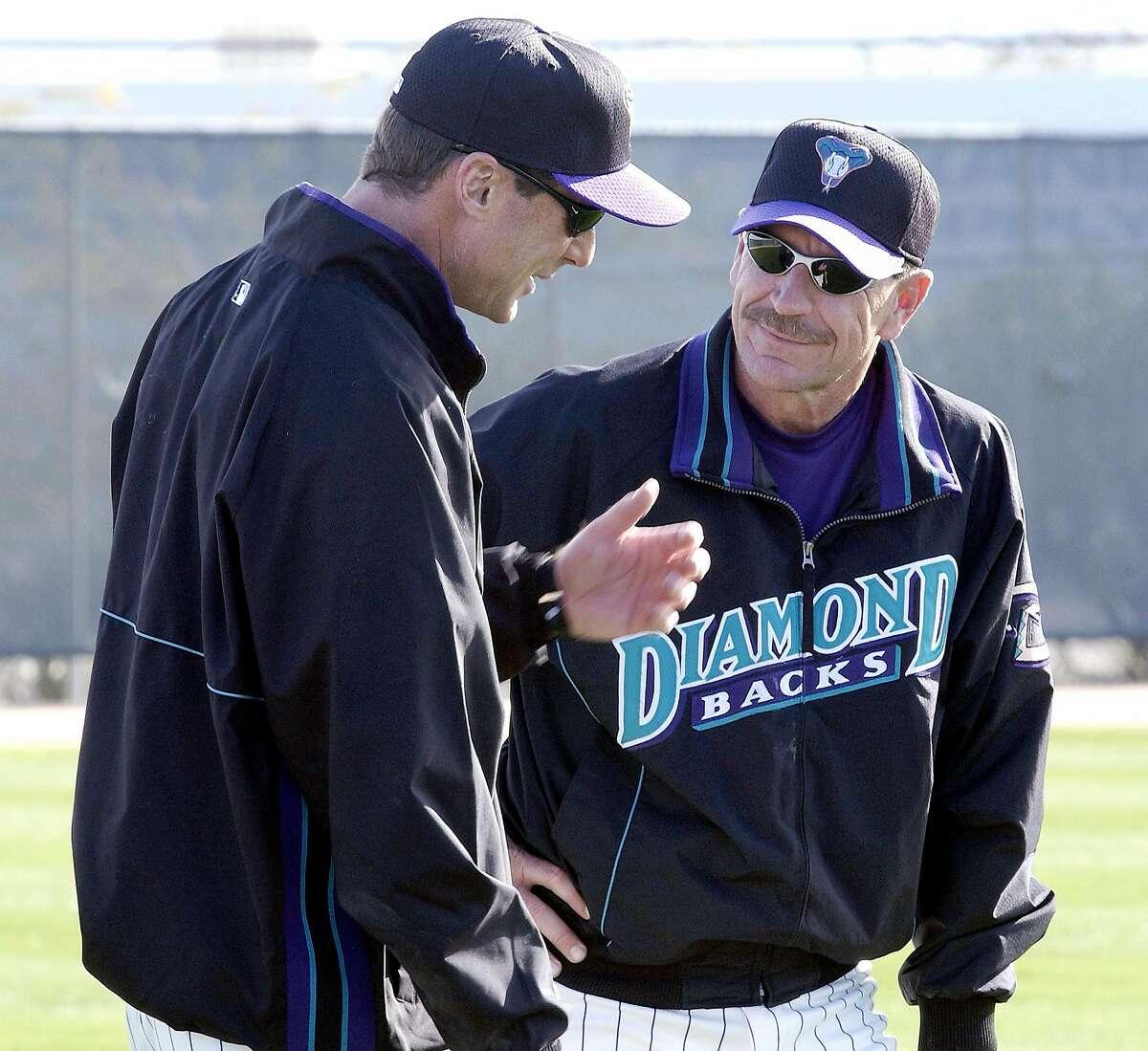 Arizona Diamondbacks' bench coach Bob Melvin (3), left, talks with manager Bob Brenly (15) during spring training workouts on Sunday, Feb. 17,2002 in Tucson, Ariz. (AP Photo/Jon Hayt)