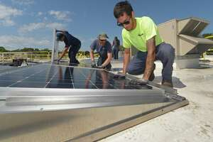 ENCON employees including C.J. Pappas, left, install solar panels on the roof of the Paul Miller Nissan dealership in Fairfield on July 18, 2018. The project received financing from Darien-based Greenworks Lending, which has been acquired by global investment manager Nuveen.