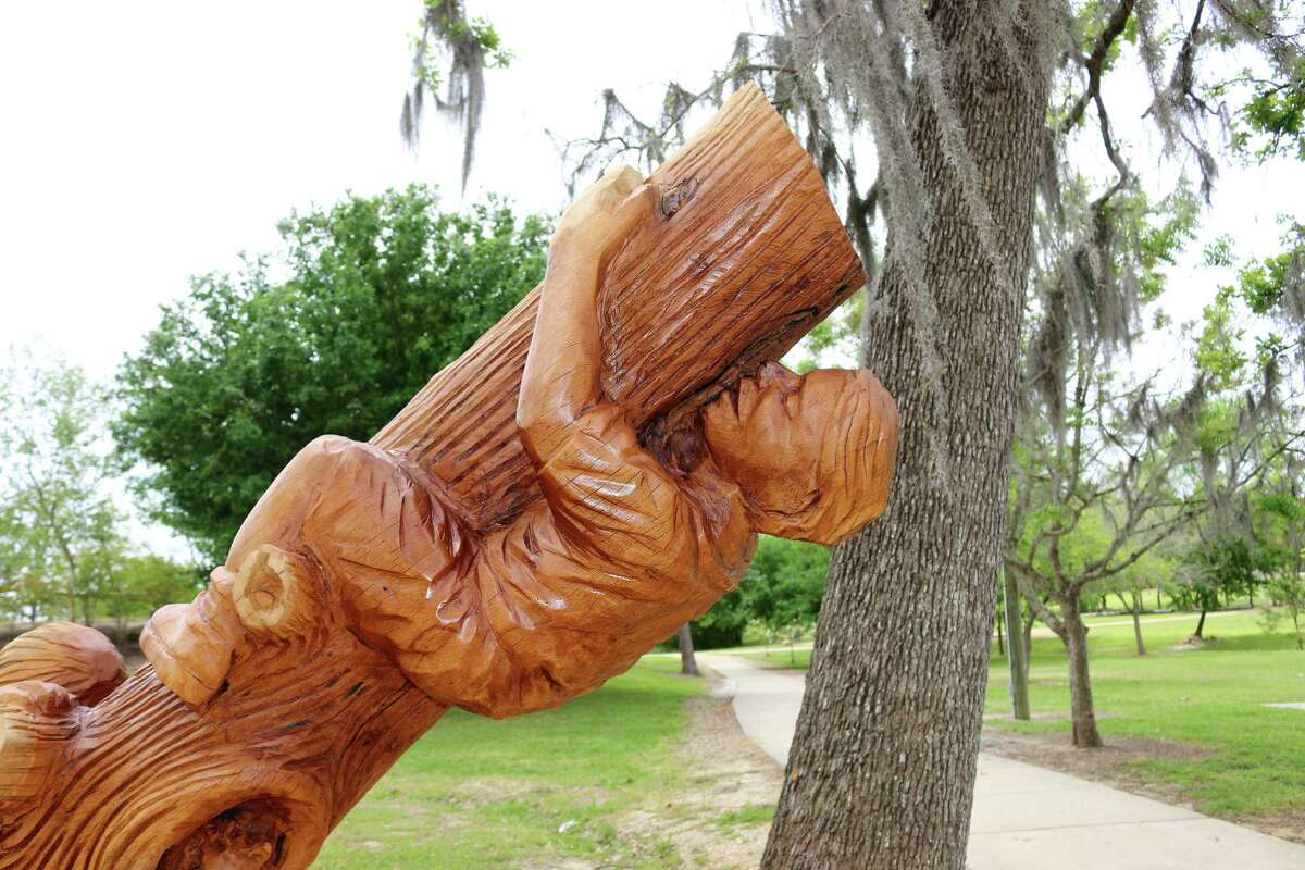 Part of the sculpture depicts a boy climbing a trunk the hard way.