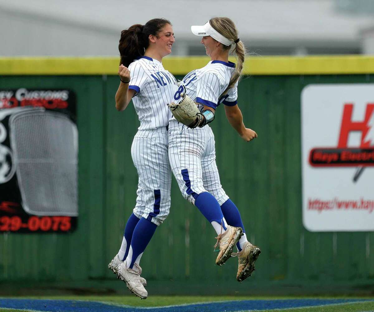 New Caney left fielder Katie Coogler (15) chest bumps right fielder Corigan Beaird (88) before the first inning of a District 20-5A high school softball game, Tuesday, April 13, 2021, in New Caney.