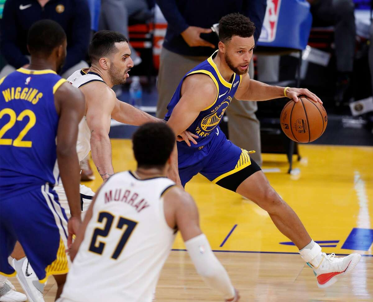 Golden State Warriors' Stephen Curry dribbles past Denver Nuggets' Facundo Campazzo during 4th quarter of Warriors' 116-107 win in NBA game at Chase Center in San Francisco, Calif., on Monday, April 12, 2021.