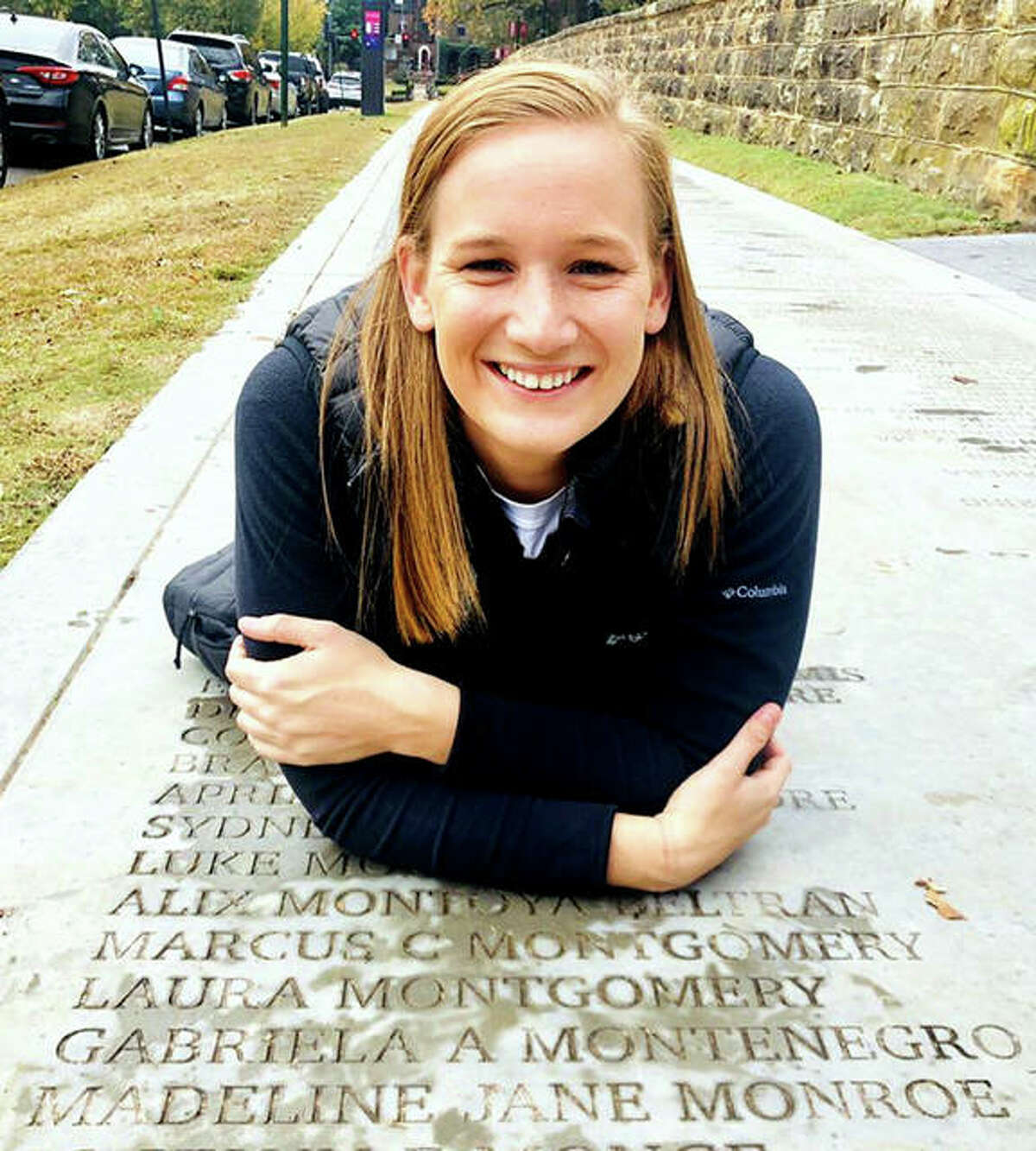 Maddie Monroe of Alton, a former standout swimmer at the University of Arkansas, is returning to coach the Summers Port Sharks swim team, with whom she started her career as a youngster. She is shown posing near her name on the 'Senior Walk' on the University of Arkansas campus.