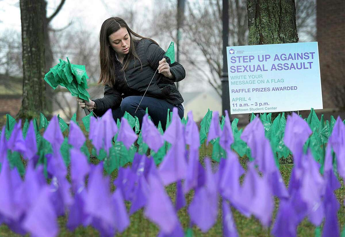 """Sydney Trezza, a counselor, plants """"awareness"""" flags at Western Connecticut State University."""