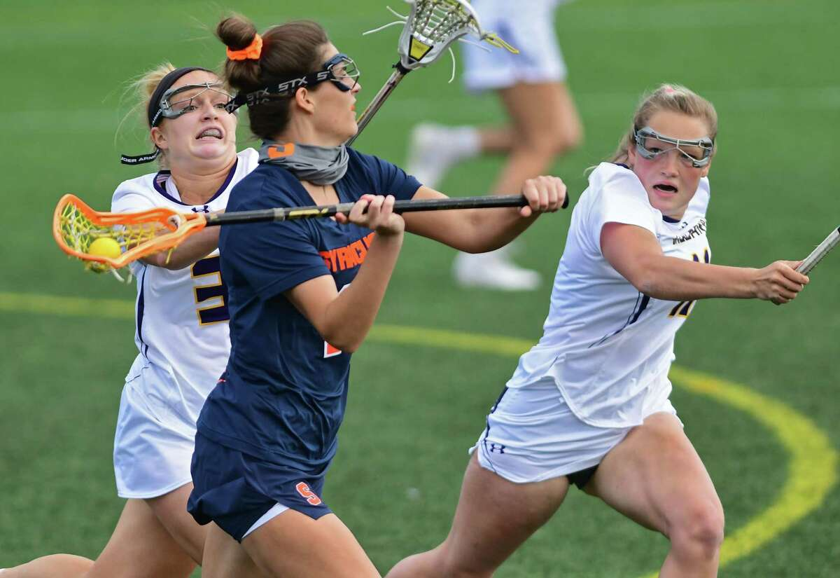 University at Albany's Madison Conway, left, and Bryar Hogg, right, defend Syracuse's Grace Fahey during a lacrosse game on Tuesday, April 13, 2021 in Albany, N.Y. (Lori Van Buren/Times Union)
