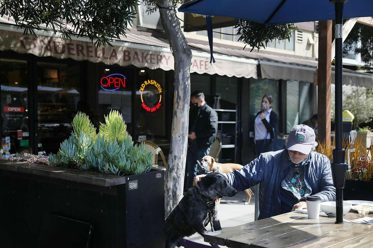 Jerry Ross pats his dog Hank as he sits in a parklet at Cinderella Bakery on Monday, April 12, 2021 in San Francisco, Calif.