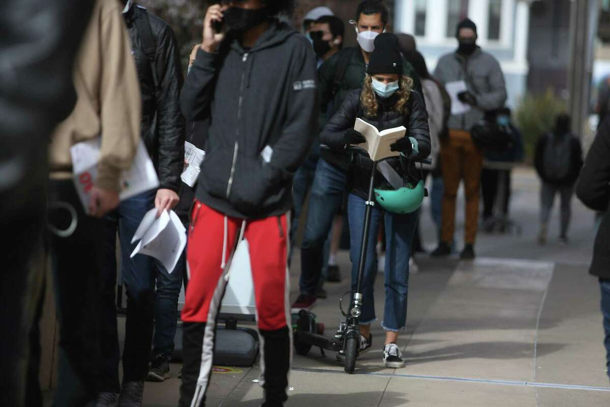 Mathilde Pons reads a book as she holds her scooter as she waits with her husband, Pierre Chesnot (behind Pons) in the line for drop-ins at the vaccine clinic at Zuckerberg General Hospital to recievie the COVID-19 vaccine on April 13, 2021 in San Francisco, Calif.