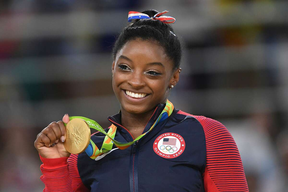 (FILES) In this file photo taken on August 16, 2016 US gymnast Simone Biles celebrates on the podium of the women's floor event final of the Artistic Gymnastics at the Olympic Arena during the Rio 2016 Olympic Games in Rio de Janeiro on August 16, 2016. (Photo by Toshifumi KITAMURA / AFP) (Photo by TOSHIFUMI KITAMURA/AFP via Getty Images)