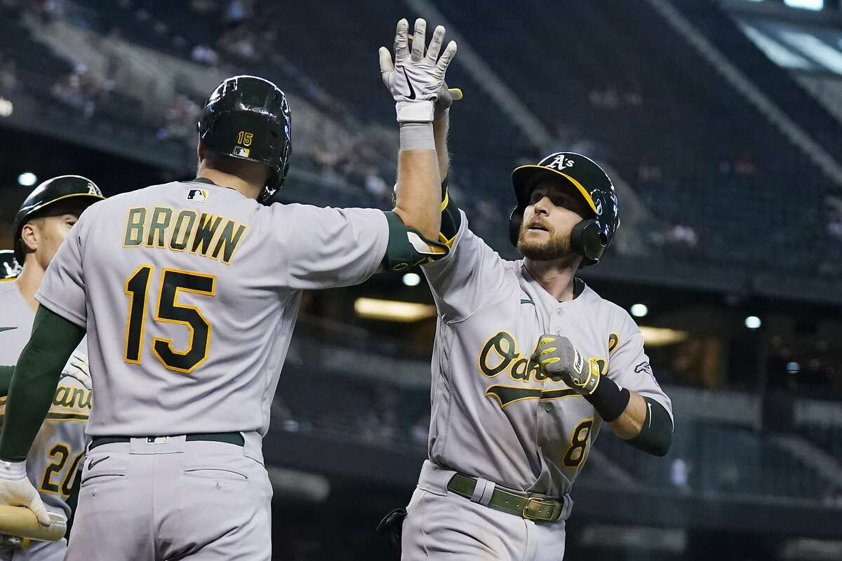 Jed Lowrie (8) celebrates his game-tying three-run home run with Seth Brown during the seventh inning.