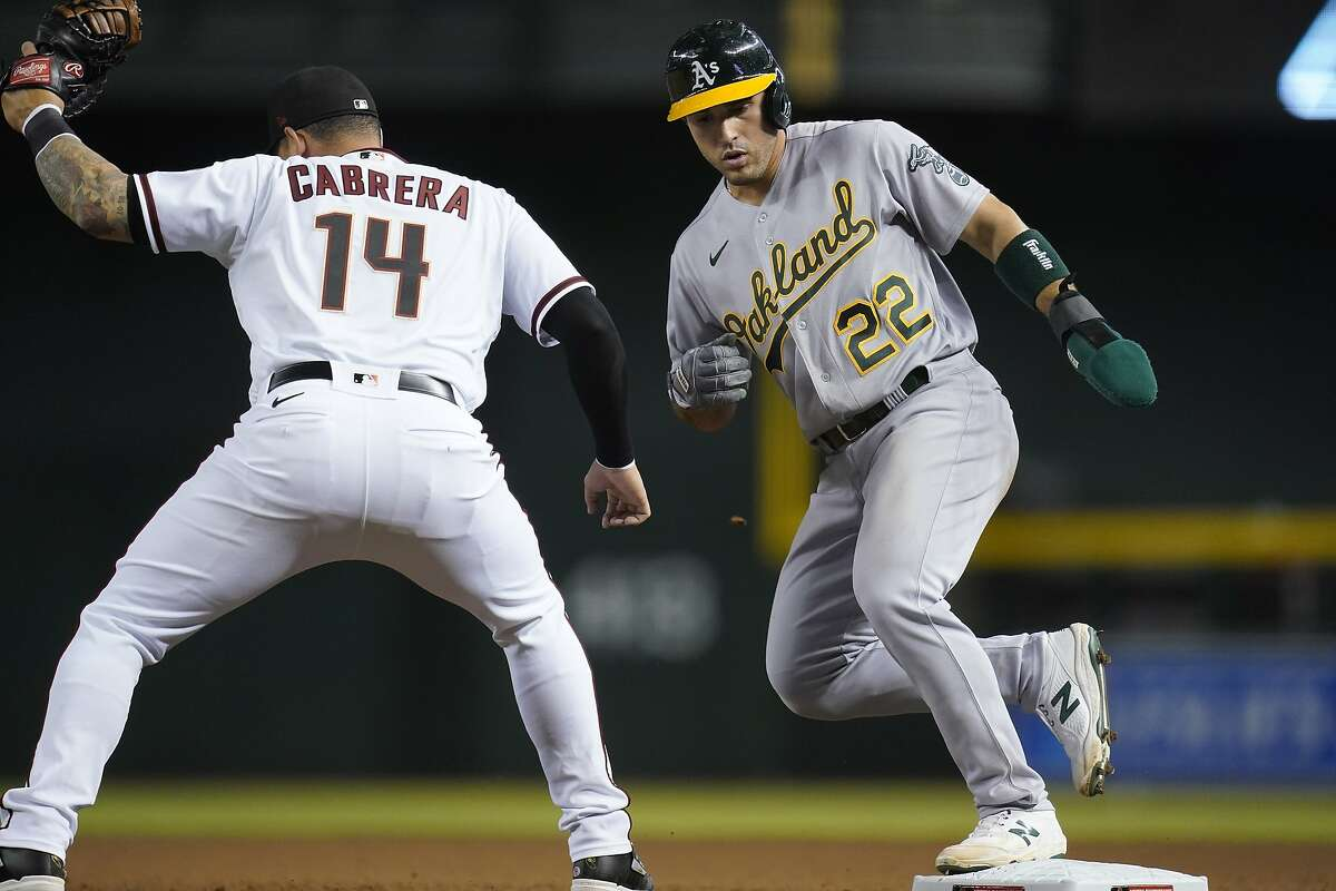 Oakland Athletics' Ramon Laureano (22) gets back to first base safely as Arizona Diamondbacks first baseman Asdrubal Cabrera (14) makes a catch on a late pickoff throw during the seventh inning of a baseball game Monday, April 12, 2021, in Phoenix. (AP Photo/Ross D. Franklin)